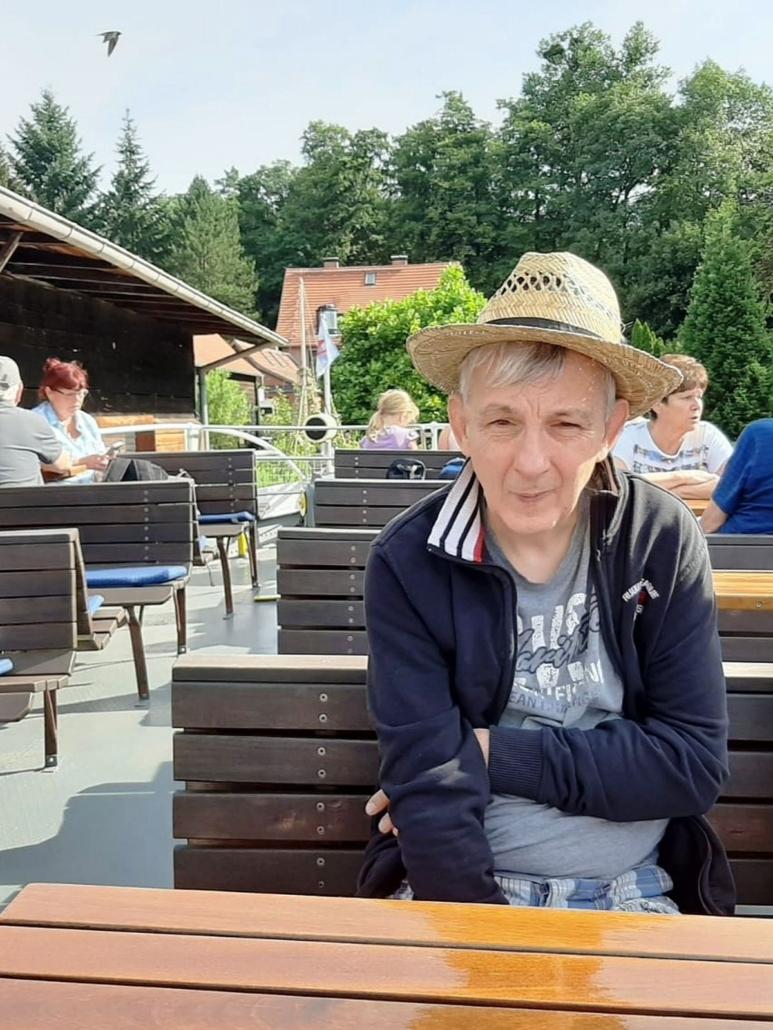 Ein Mann sitzt auf dem Oberdeck´des Schiffes an einem Tisch. Er hat einen Strohhut auf dem Kopf. Im Hintergrund sind am Ufer Bäume und ein Haus zu erkennen.
