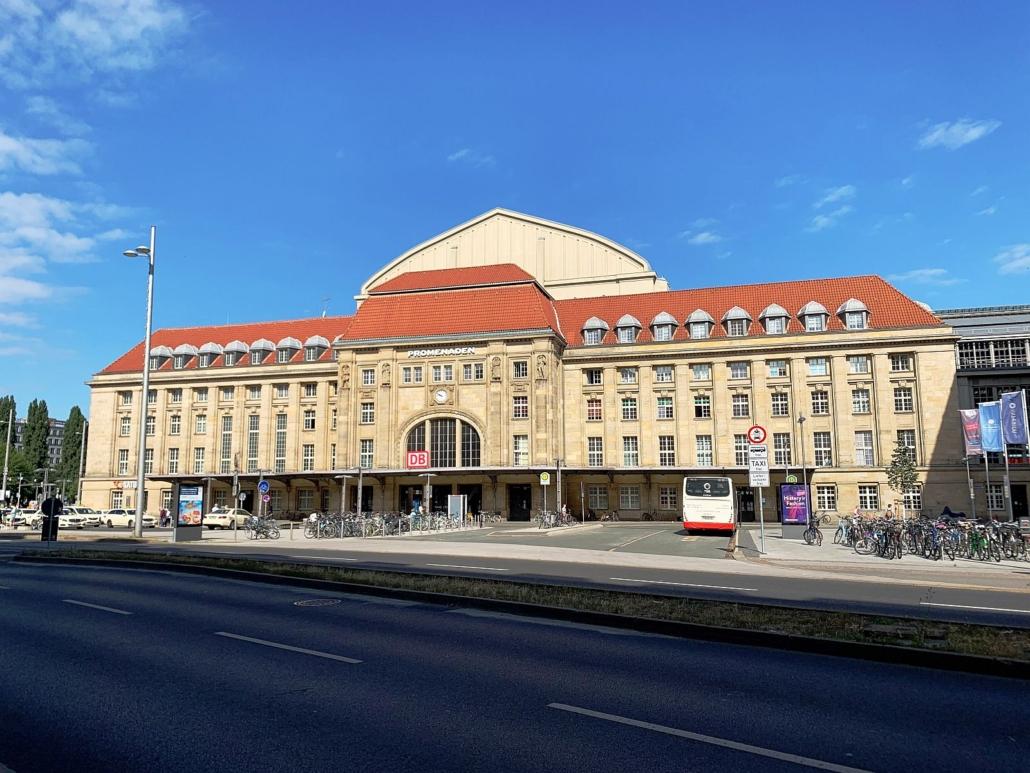 Blick auf einen Nebeneingang des Leipziger Hauptbahnhofes.. Die Fassade ist aus hellem Sandstein. In der Mitte ist das Eingangsportal, rechts und links viergeschossige Seitenflügel mit ausgebautem Dachgeschoss.