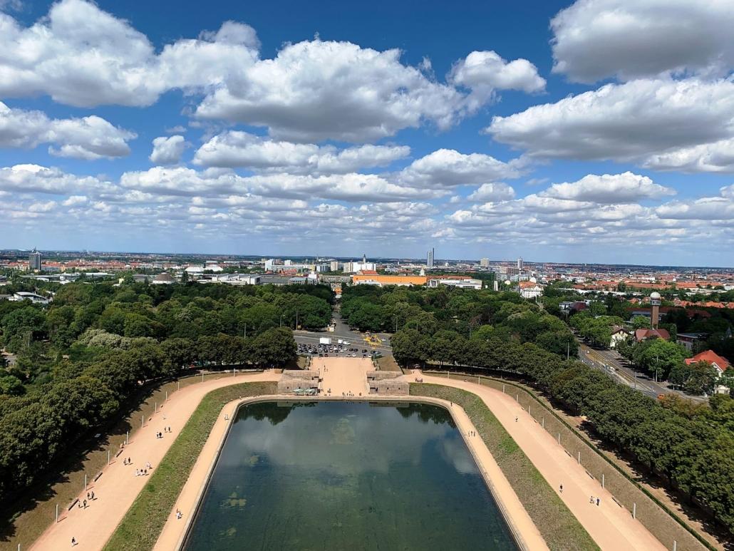 Im Vordergrund ist das große Wasserbecken am Fuße des Völkerschlachtdenkmals zusehen. Im Wasser spiegeln sich der Himmel. und die Umgebung. Hinter einem Park ist Leipzig zusehen. In der Mitte ragt das City-Hochhaus heraus.