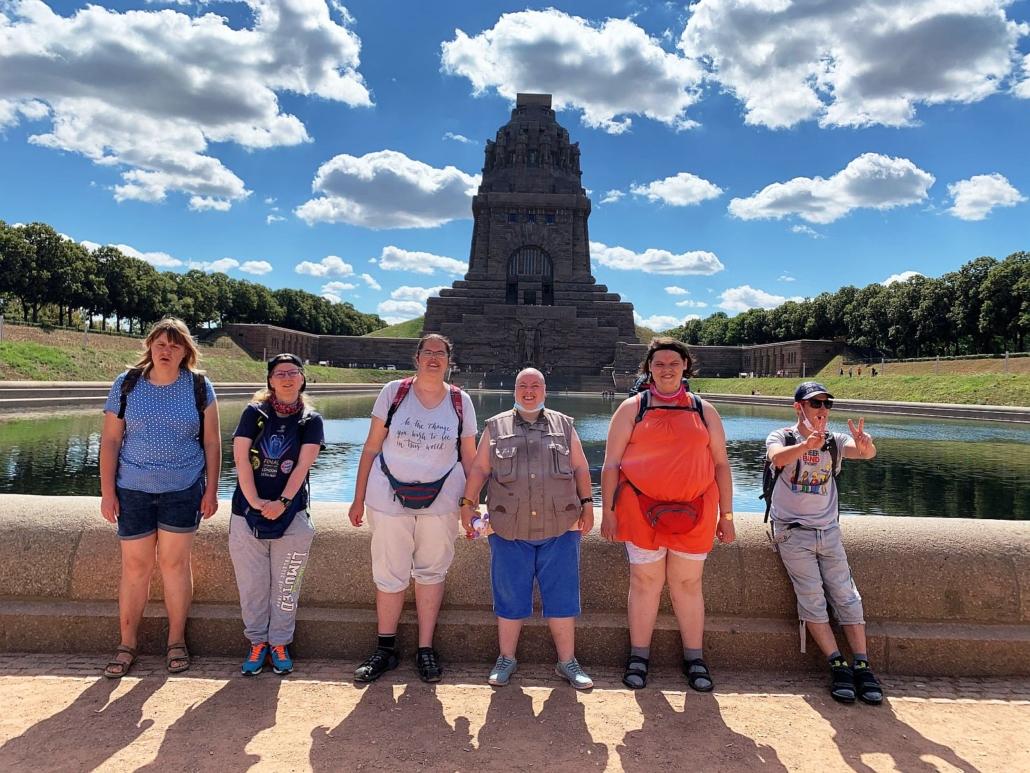 Fünf Frauen und ein Mann aus der Reisegruppe stehen am Rand des Wasserbeckens. Im Hintergrund ragt das Völkerschlachtdenkmal in den blauen Himmel mit kleinen weißen Wolken.
