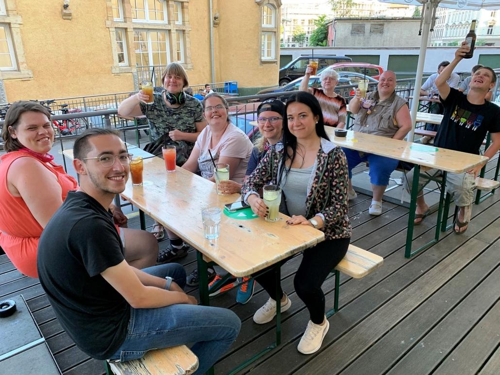 Auf der Holzterrasse eines Restaurants sitzen die insgesamt sechs Frauen und zwei Männer der Reisegruppen an zwei Bierzeltgarnituren. Mit unterschiedlichen Getränken prosten sie in Richtung Kamera.