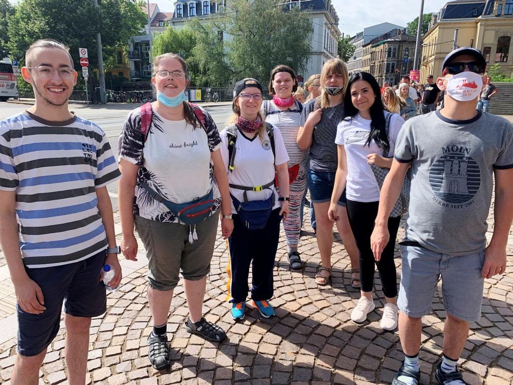 Die Reisegruppe hat sich nach dem Einkaufsbummel auf einem gepflasterten Platz zum Abschiedsfoto aufgestellt. Dazu gehören fünf Frauen und zwei Männer. Der Mann rechtsaußen trägt eine Maske. Im Hintergrund sind mehrere große Altbauten zu sehen.