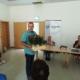 Manfred Groth steht mit einer Stiege mit Blumen in beiden Händen. Er wendet sich den Mitgliedern zu.