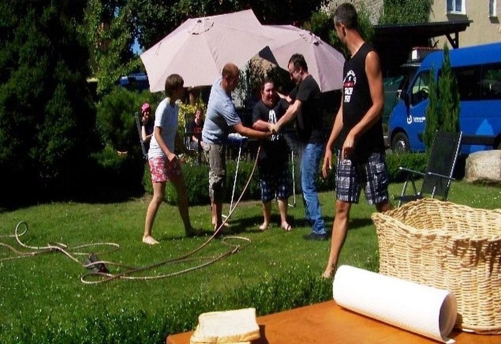Mehrere Personen versuchen sich auf dem Rasen gegenseitig mit dem Wasserschlauch zu bespritzen.