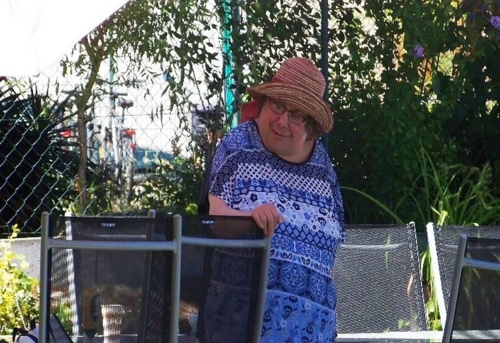 Eine Frau mit Brille und buntem Strohhut hält sich an einer Stuhllehne fest. Sie beobachtet das Geschehen um sich herum.