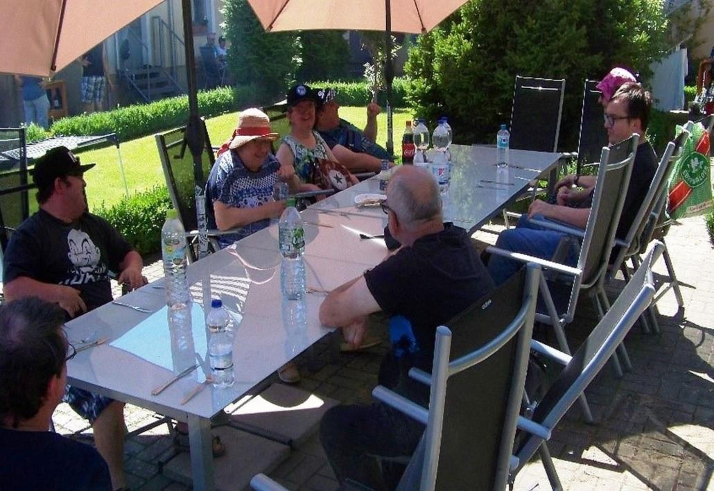 Der Tisch ist mit großen Wasserflaschen und Besteck gedeckt. Darum herum sitzen mit Abstand zueinander drei Frauen und fünf Männer.