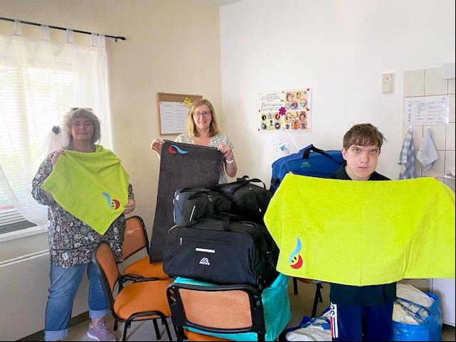Im Vordergrund halten Frau Bester und ein jugendlicher Bewohner je ein apfelgrünes Handtuch in den Händen. Dahinter zeigt Frau Bollgehn ein anthrazitfarbenes.