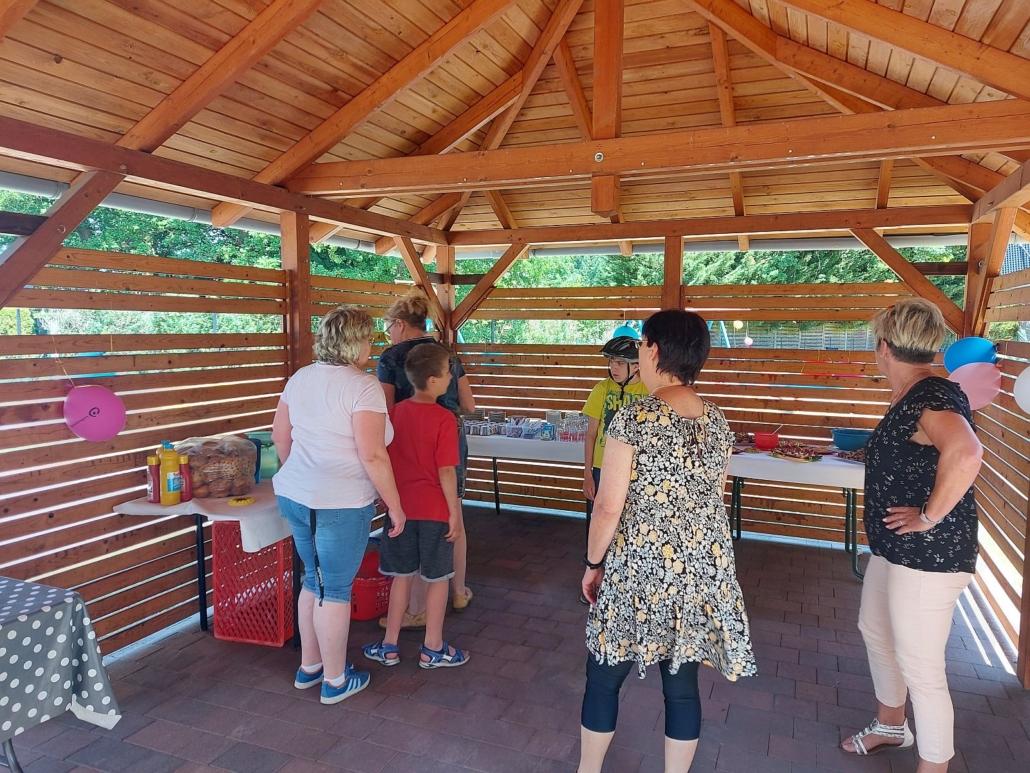 Unter einem großen Holzpavillon ist im rechten Winkel eine Tafel mit Getränken, kleinen Häppchen, Gläsern und Besteck aufgebaut worden. Davor stehen vier Betreuerinnen und zwei Kinder.