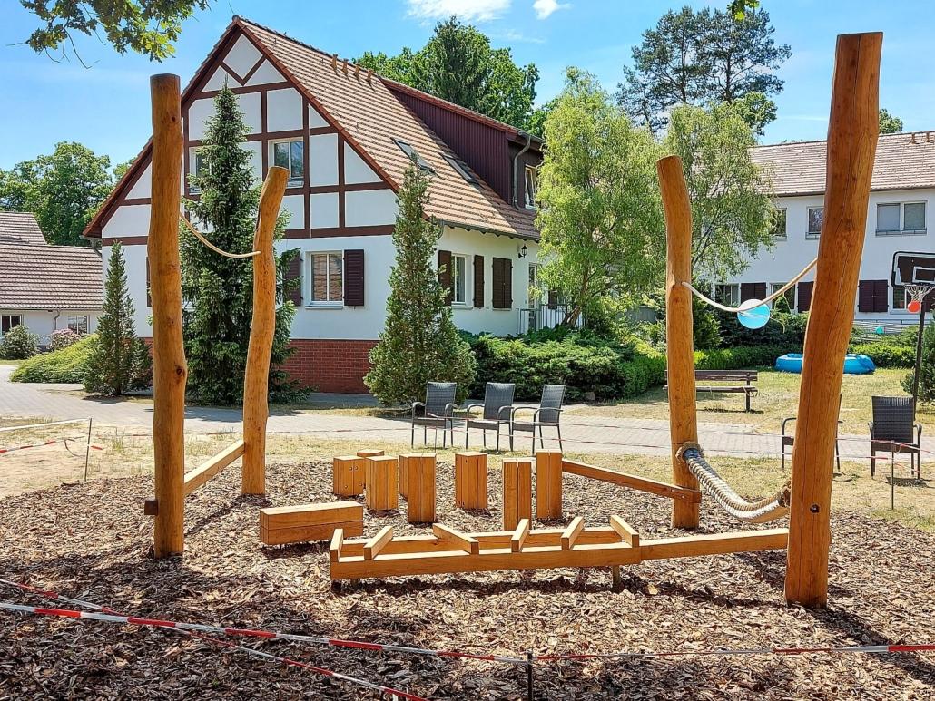 Die Bewegungslandschaft besteht aus vier stabilen, ca. 2 Meter hohen, endrindeten Naturholzstämmen, die im Rechteck angeordnet sind. Jeweils zwischen zweien ist oben ein dünneres Seil gespannt. Unten ist auf der eine Seite ein ganz dickes Seil befestigt und auf der anderen Seite eine viereckige, stabile Holzlatte. Innerhalb des Vierecks sind verschieden hohe, senkrechte Holzblöcke und andere Balancier Möglichkeiten aufgestell.t Der Boden ist dick mit Rindenmulch bedeckt.
