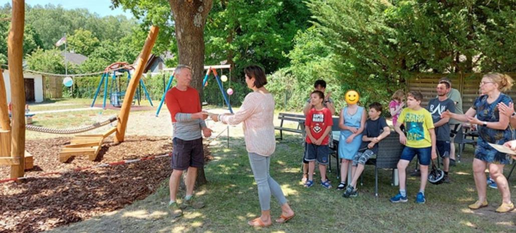 Die Wohnstättenleiterin des Kinder- und Jugendbereiches, Frau Bollgehn, übergibt auch an den Lehrmeister und Bauleiter ein kleines Geschenk. Alle Anwesenden klatschen Beifall.