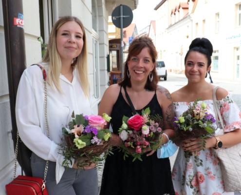 Die drei erfolgreichen Absolventinnen Julia Schmidt, Silvana Köthen und Lisa-Maria Goldberg stehen nebeneinander und lächeln. In den Händen halten sie Blumensträuße.