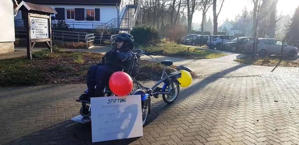 Herr K. sitzt im Rollstuhl, der auf der Plattform vorn am Rollstuhlfahrrad befestigt ist. Vorn links steht das Schild mit dem Dank an die Stiftung. Am Fahrrad sind vorn ein roter und hinten ein gelber Luftballon befestigt. Herr K. ist warm angezogen und trägt einen Fahrradhelm über seiner Mütze. Im Hintergrund sind Gebäude der Wohnstätte zu sehen.