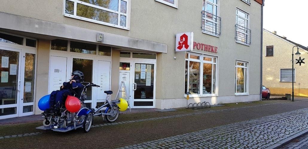 Die Apotheke ist in einem neugebauten Gebäude untergebracht. Der Zugang ist barrierefrei. Herr K. steht in der Mitte zwischen zwei Eingängen.