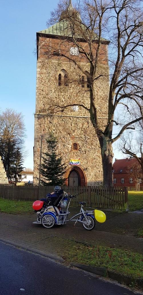 Der Feldsteinturm der Groß Schönebecker Kirche ragt in den blauen Himmel. Das Rollstuhl-Bike mit Herrn K. steht am Zaun, hinter dem ein großer, kahler Laubbaum steht.
