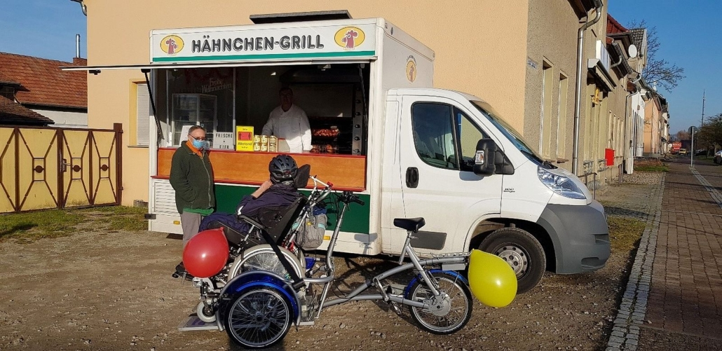 Das Fahrrad mit Herrn K. steht vor einem mobilen Hähnchengrill. Herr K. schaut in Richtung des weißen Transporters vor dem ein Mann mit Gesichtsmaske steht. Der Verkäufer mit seinem weißen Kittel ist im inneren des Wagens zu sehen.