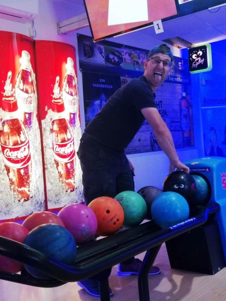 Max, ein junger Mann mit dunkler Hose, schwarzem T-Shirt und einem dunkelblauen Basecap , greift sich gerade ein Bowlingkugel. Er hat den Kopf in Richtung Kamera gedreht und steckt die Zunge raus.