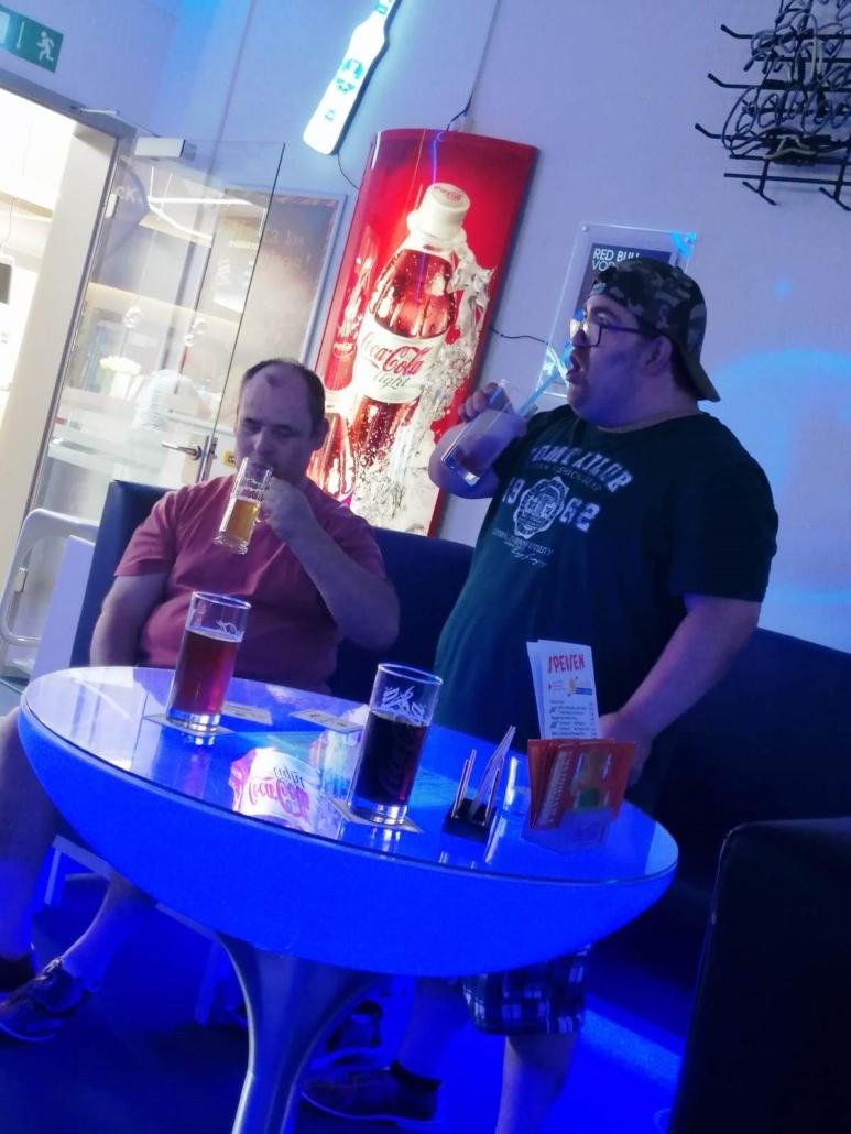 Die zwei jungen Männer trinken aus ihren Gläsern. Der eine hat ein alkoholfreies Bier, der andere ein Milchgetränk.
