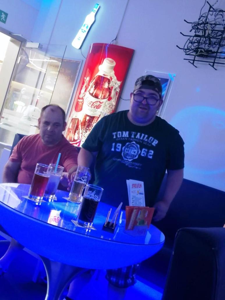 Zwei junge Männer, der rechte mit dunklem Basecap, sitzen an einem runden Tisch, auf dem Getränke stehen.