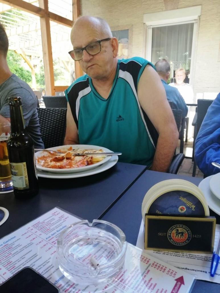 Vor Hans, dem ältere Mann, steht sein fast leerer Teller mit Pasta. Das Besteck liegt noch in Arbeitsstellung. Er sieht nachdenklich. aus.