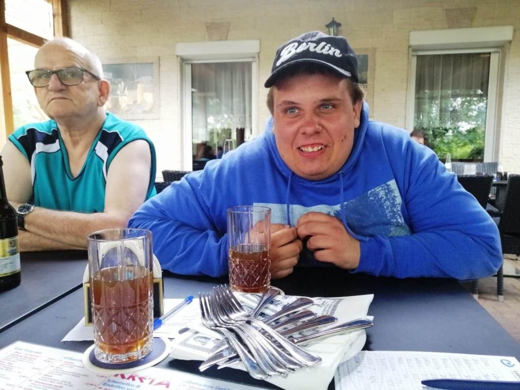 Ein älterer und ein jüngerer Mann (Hans und Rocco) sitzen am Tisch mit einem Getränk vor sich. Vor Rocco steht ein Teller mit Besteck.
