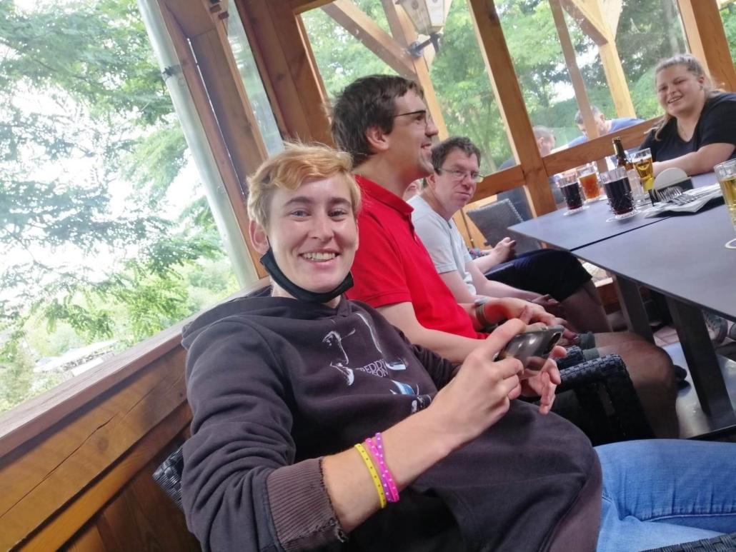 Zwei Frauen und zwei Männer sitzen am Tisch und haben Getränke vor sich stehen. Die junge Frau ganz vorn strahlt in die Kamera und hat ihr Handy in der Hand.