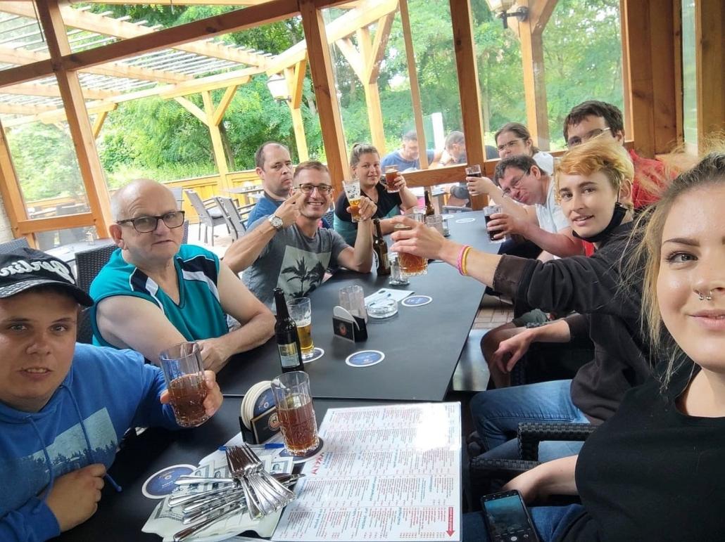 Die gesamte Wohngruppen sitzt in einem Restaurant an mehreren zusammengestellten Tischen. Fast alle halten ein Getränk in der Hand und prosten in die Kamera.