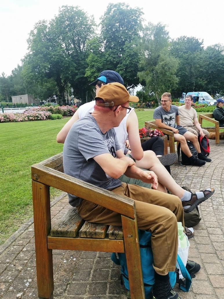 Auf zwei Holzbänken in der Nähe der Dampfer-Anlegestelle siezten vier junge Männer. Die beiden auf der 1. Bank tragen Basecaps. Alle haben Rucksäcke dabei. Im Hintergrund sind Rasen und eine Blumenrabatte zu sehen.