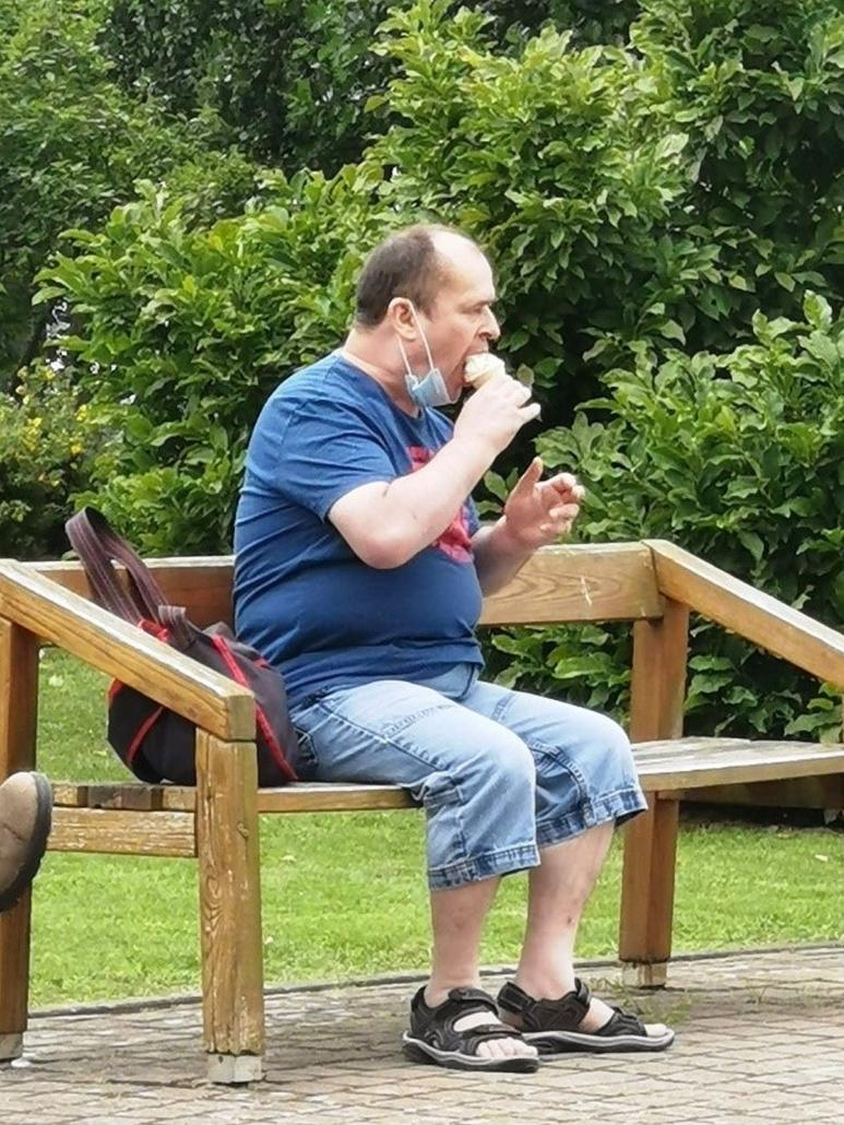 Ein junger Mann sitzt auf einer Holzbank und lässt sich ein Softeis schmecken. Er hat kurze blaue Jeans und ein blaues T-Shirt an.