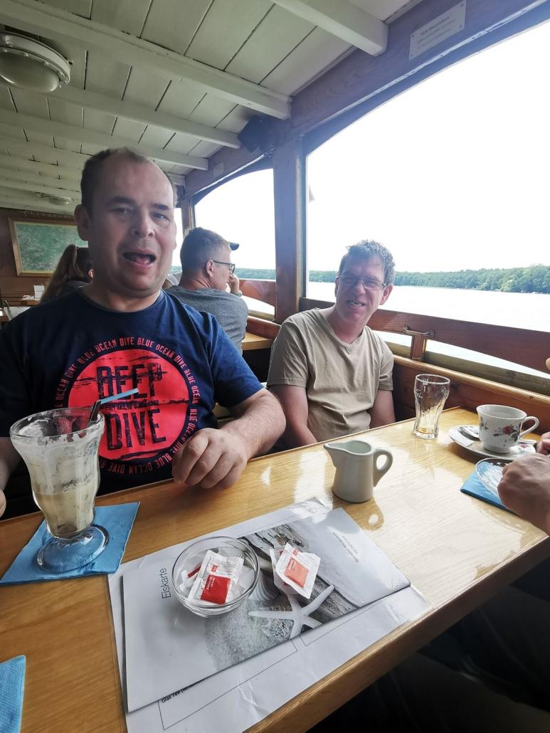 Unter Deck sitzen zwei junge Männer an einem Holztisch. Vor ihnen stehen leere Tassen und Gläser. Aus dem geöffneten Fenster sieht man das bewaldete Ufer des Werbellinsees.