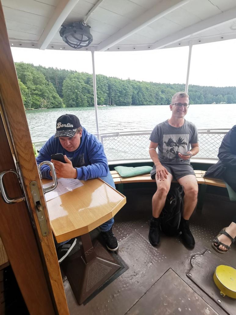 Zwei junge Männer sitzen am Heck des Ausflugdampfers auf dem Werbellinsee. Max sitzt am Tisch, Rocco an der Reling. Beide haben ein Handy in der Hand. Im Hintergrund sind Wasser und das Ufer des Werbellinsees zu sehen.