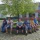 Fünf Männer und ein junge Frau aus der Wohngemeinschaft Breite Straße 21 sitzen auf der runden Einfassung eines Baumes auf dem Eberswalder Richterplatz. Die meisten tragen T-Shirts und kurze Hosen. Im Hintergrund ist noch ein Teil des Gebäudes der Wohngemeinschaft Mauerstraße 21 zusehen.