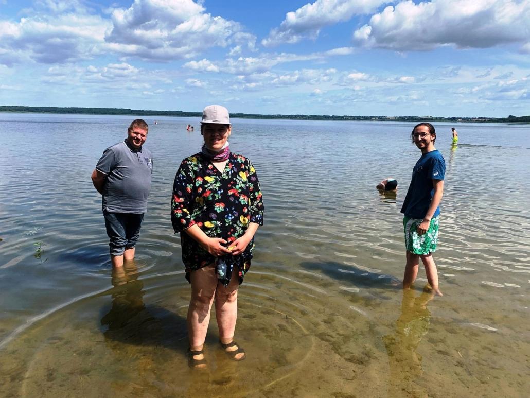 Mit den Füßen im Grimnitzsee erfrischen sich eine Frau und zwei Männer. Der Himmel ist blau mit vielen kleinen weißen Wölkchen. Weiter hinten im Wasser sieht man andere Badegäste.