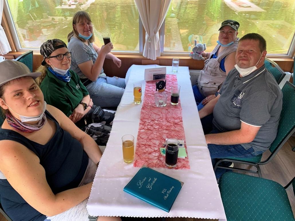 Im Salon (unter Deck) des Fahrgastschiffes sitzen vier Frauen und ein Mann um einen schmalen rechteckigen Tisch mit weißer Tischdecke. Vor ihren stehen Getränke. Durch die Fenster ist die Wasseroberfläche zu sehen.
