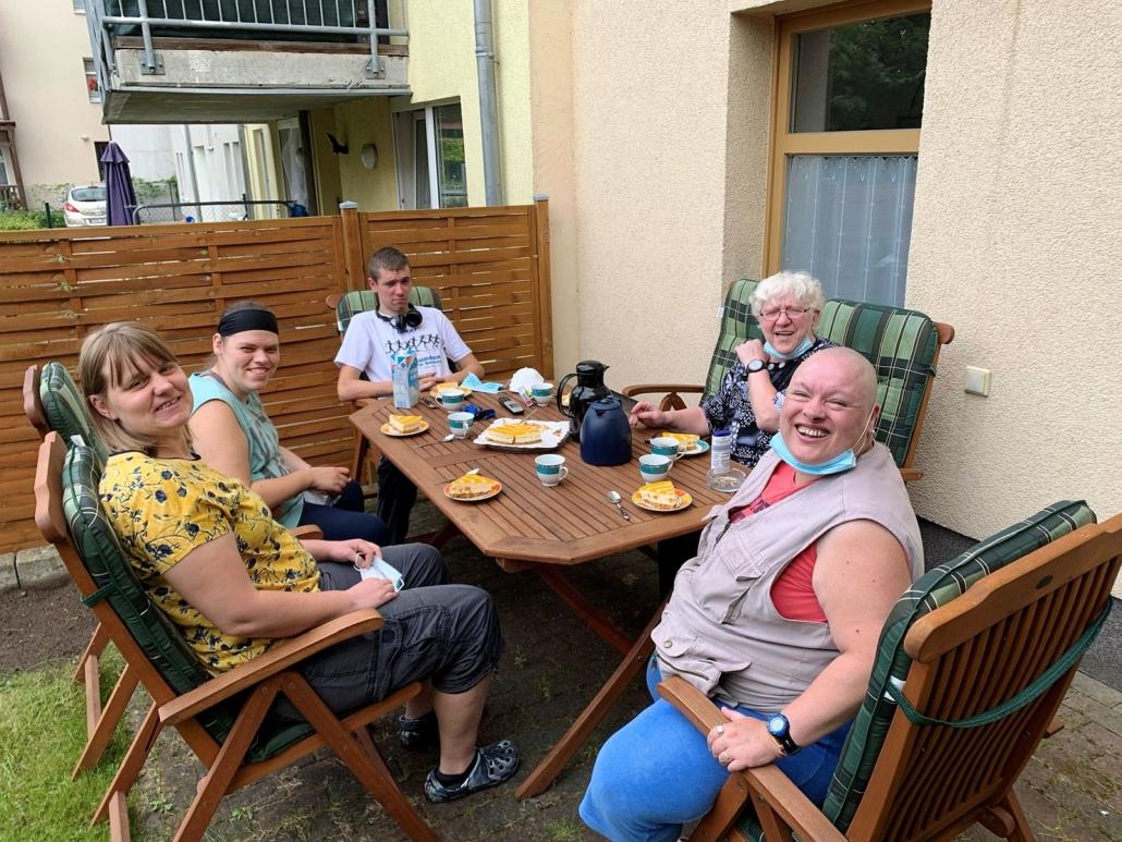 An einem Holztisch auf der gepflasterten Terrasse trinken vier Frauen und eine Mann Kaffee. Alle haben einen Teller mit zwei Stück Kuchen vor sich. Die Frau lächeln, aber der junge Mann runzelt die Stirn.