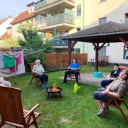 Vier Bewohnerinnen und ein Bewohner sitzen auf Stühlen im Kreis um eine Feuerschale im Hof der Jüdenstraße 7. Ein Stuhl im Vordergrund ist frei. Neben der Feuerschale steht eine hellgrüne Plastegießkanne. Auf einer Wäschespinne hängt Wäsche.
