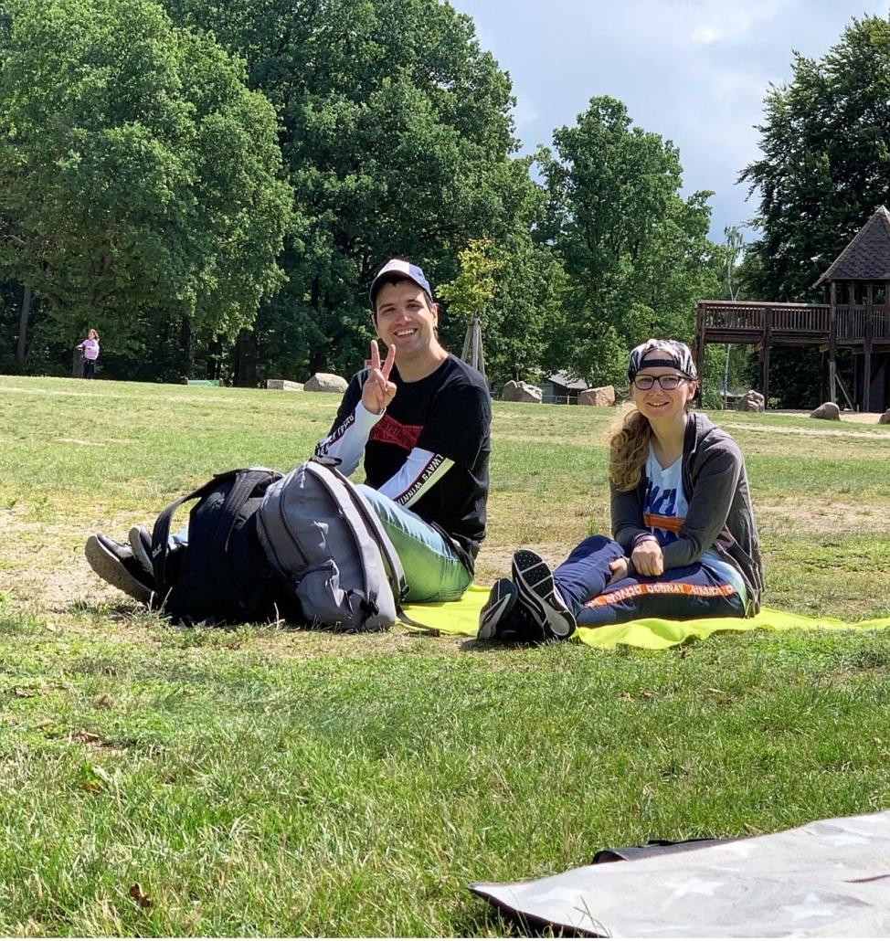 Eine junge Frau und ein junger Mann sitzen auf einer Decke auf der Liegewiese am Seezeit-Resort (ehemals Pionierrepublik, EJB). Der jung Mann zeigt mit der rechten Hand das Victory-Symbol.