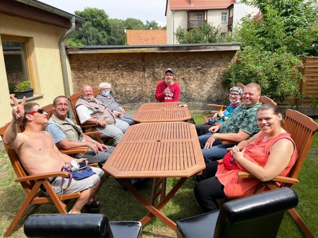 Fast alle Bewohner der Wohngruppen sind an zwei Holztischen im Hof versammelt. Die Sonne scheint und alle lachen bzw. lächeln in die Kamera. Einer macht das Viktory-Zeichen mit der rechten Hand.
