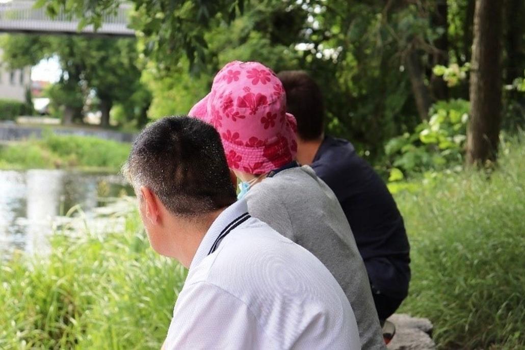 Drei Personen sitzen auf einer Bank ohne Lehne am Ufer eines Gewässers. Die Bank ist von Gras und Bäumen umgeben.