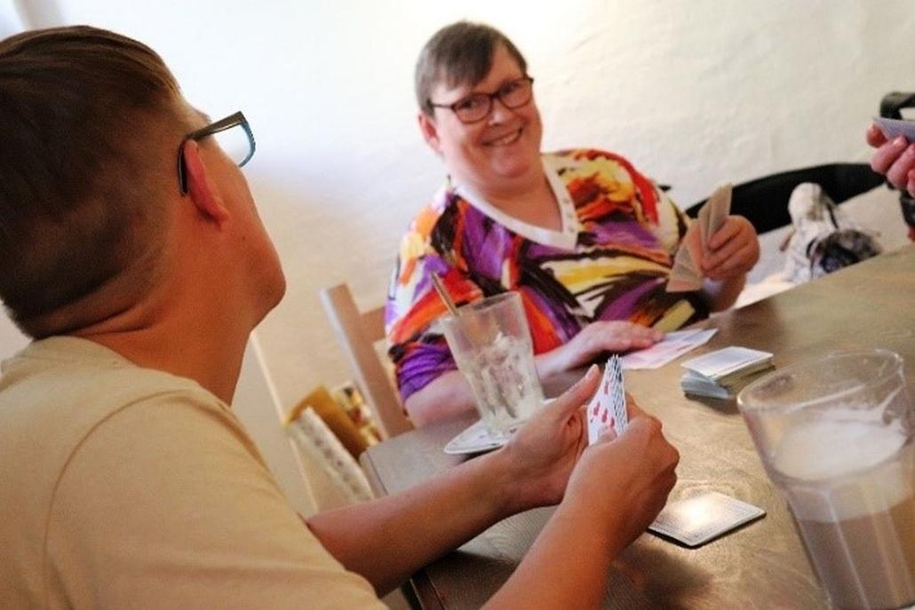 Eine Frau sitzt mit ihren Spielkarten in der linken Handlächeln am Tisch. Die andere Hand liegt auf mehreren Karten vor ihr. Sie blickt lächelnd auf einen Mitspieler, der rechts von ihr sitzt.