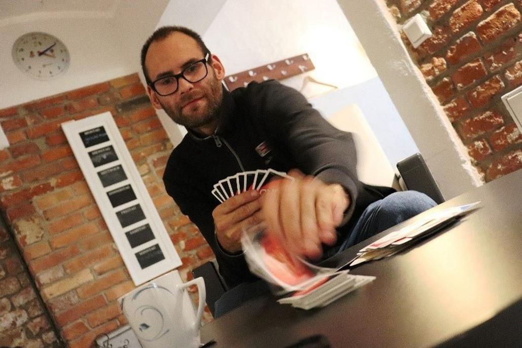 Ein junger Mann mit Brille und kurzem Vollblatt sitzt an einem runden Tisch. In der rechten Hand hält er acht Spielkarten. Mit der linken Hand zieht er eine von einem Kartenstapel.