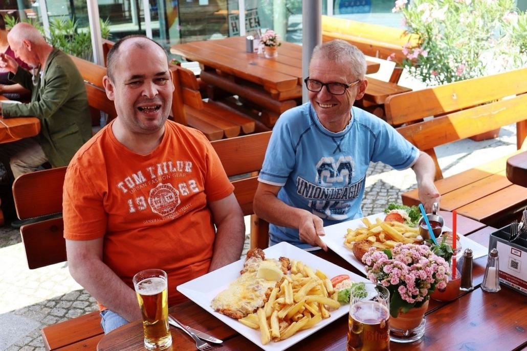 Zwei Männer sitzen im REDO XXL Restaurant. Vor sich haben sie jeder einen riesige Portion Pommes frites mit einem XXL-Schnitzel. Beide lachen.