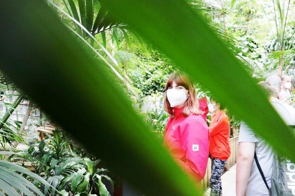 Eine junge Frau mit Maske steht an einem Geländer und blickt in die Kamera. Sie wird im Vordergrund von zwei Blättern umrahmt. Im Hintergrund sind verschiedene Pflanzen zu sehen.