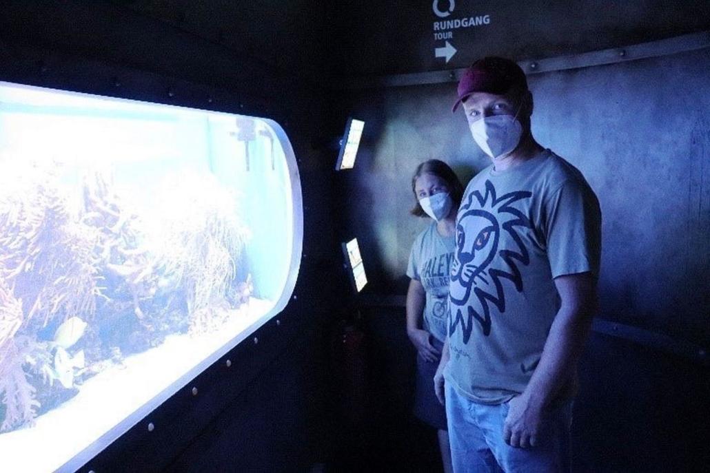 Eine junge Frau und ein junger Mann schauen in die Kamera. Sie stehen seitlich zu einem großen ovalen Fenster, hinter dem Fische, Wasserpflanzen und Korallen zu sehen sind.