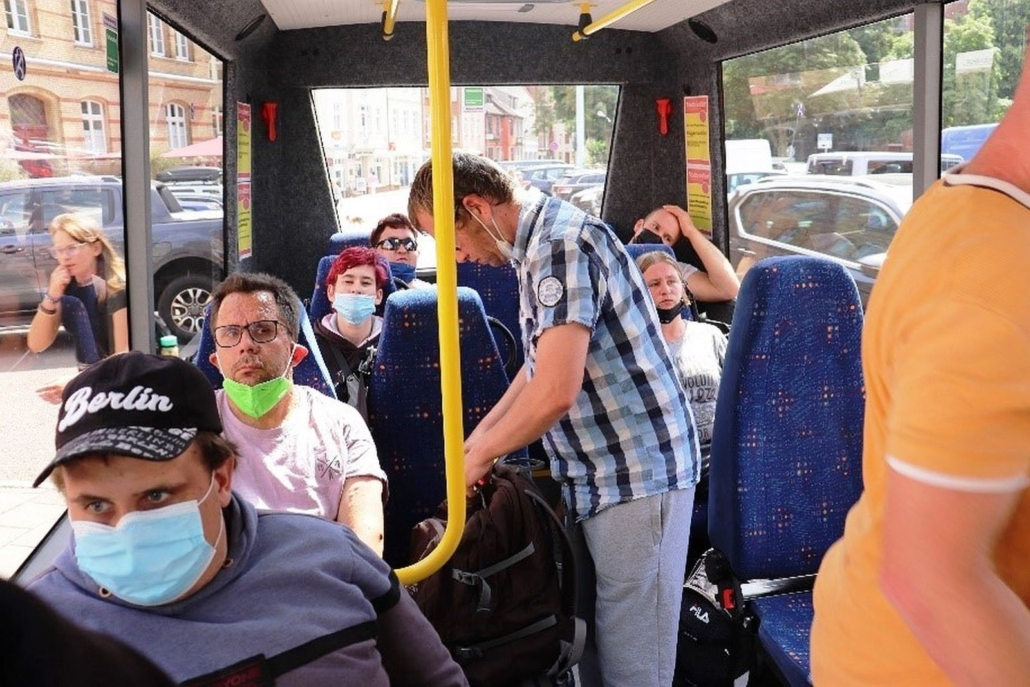 Die Reisegruppe sitzt in einem Bus mit großen Fenstern. Die meisten trage Maske. Durch die Fenster sieht Gebäude und parkende Autos.