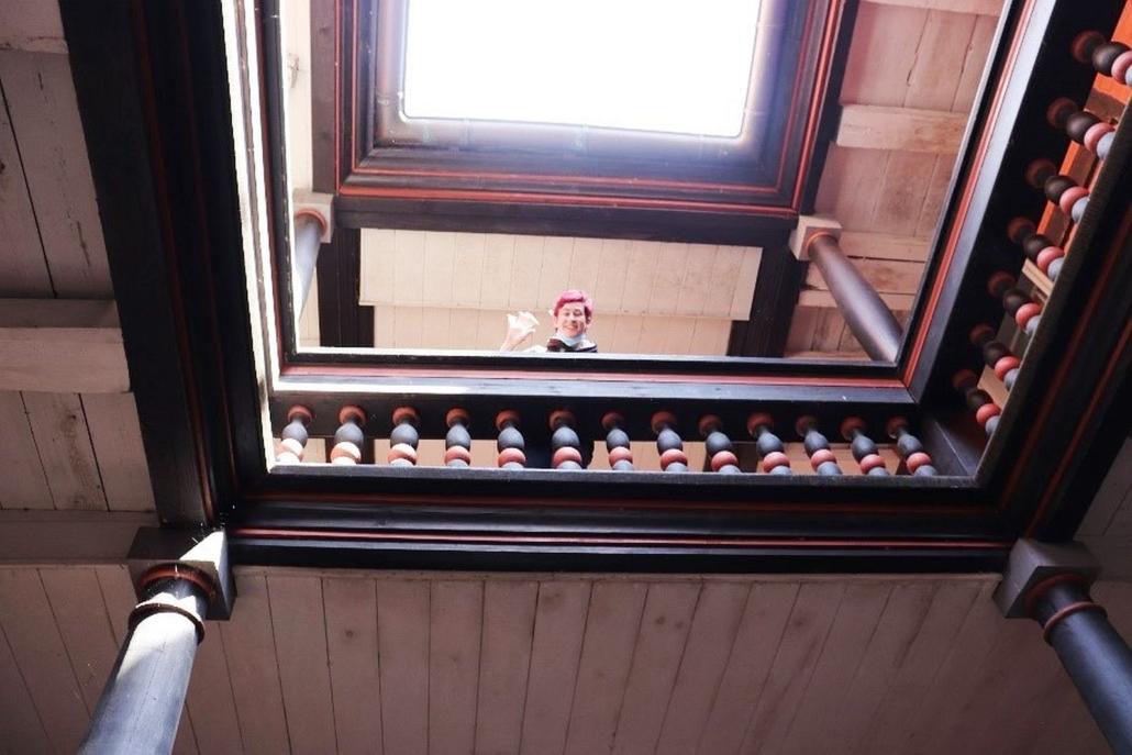 Eine junge Frau schaut lächelnd und winkend im oberen Stockwerk eines Gebäudes über die schwarz-rote Brüstung.