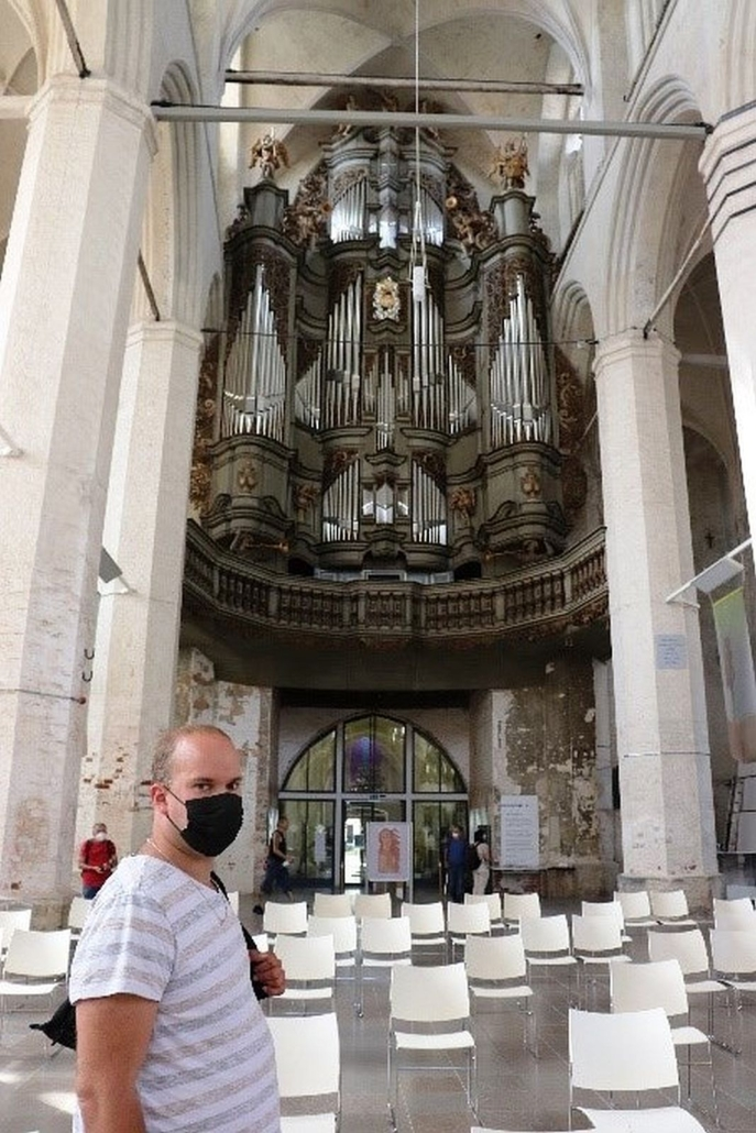 Am Ende der hellen Kirche ist eine große Orgel zu sehen. Davor stehen weiße Stühle mit Abstand zu einander. Ganz vorn ist ein Mann aus der Reisegruppen zu sehen. Er trägt eine schwarze Maske.