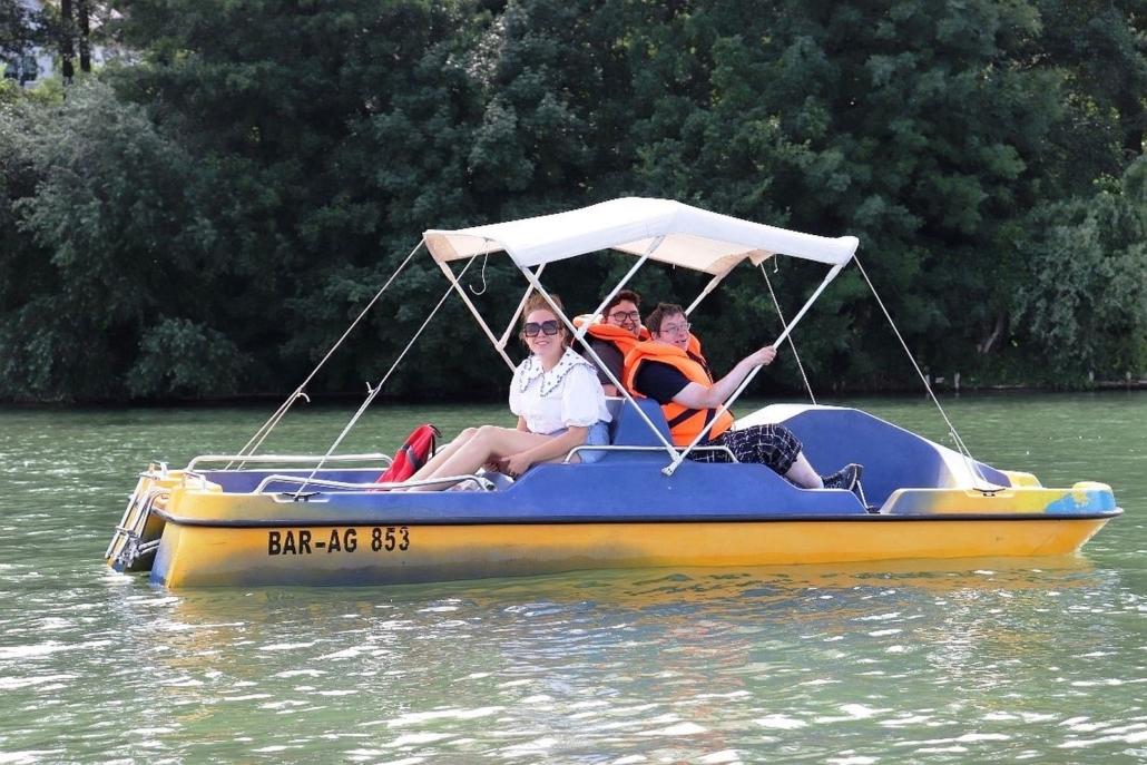 Zwei junge Männer fahren mit ihrer Betreuerin in einem blau-gelben Tretboot auf dem Werbellinsee. Die beiden Männer tragen orangene Schwimmwesten.