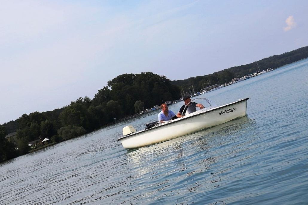 Zwei Männer fahren mit einem weißen Motorboot auf dem Werbellinsee. Der ältere steuert das Boot. Er hat eine Schirmmütze auf.