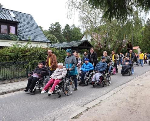 Auf der Straße des Dr.-Zinn-Weges läufen und rollen die Bewohnerinnen und Bewohner der Wohnstätte Sonnenhof, angeführt von sieben Rollifahrern mit ihren Begleitern der Deutschen Post. Alle sind warm angezogen. auf der linken Seite sind Einfamilienhäuser zusehen.